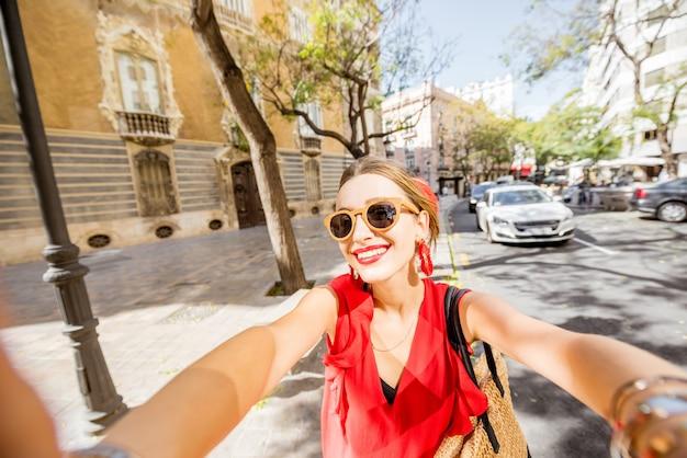 Jonge vrouw toerist in rode jurk selfie foto maken reizen in de oude stad van de stad valencia, spanje