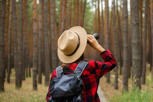 Jonge vrouw toerist met rugzak, hoed en rood geruit overhemd en kijkt door een verrekijker in het bos.
