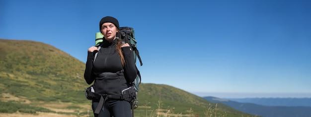 Jonge vrouw toeristische wandelaar met een grote rugzak staat op de top van de berg