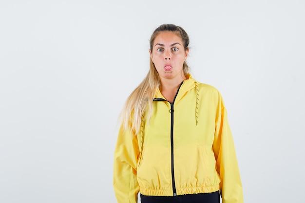 Jonge vrouw tong uitsteekt in gele regenjas en op zoek raar