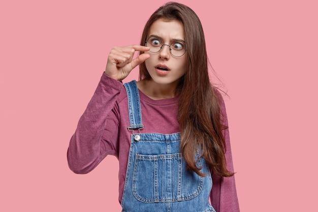 Jonge vrouw toont een kleine hoeveelheid van iets, toont een niet-indrukwekkende grootte, vormt een klein ding, heeft een angstige uitdrukking