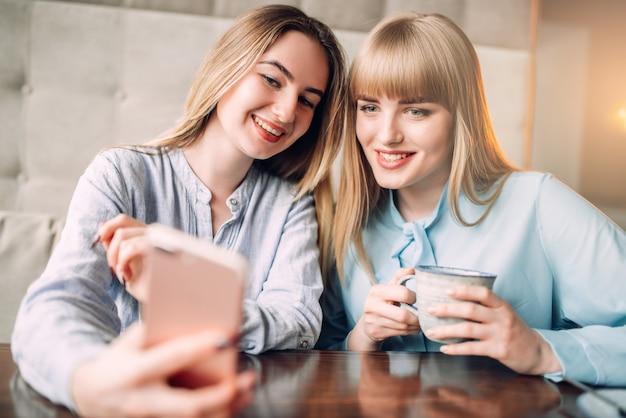 Jonge vrouw toont foto's op telefoon aan haar vriendin in café. vriendinnen vrije tijd in restaurant, roddelaars bijeen