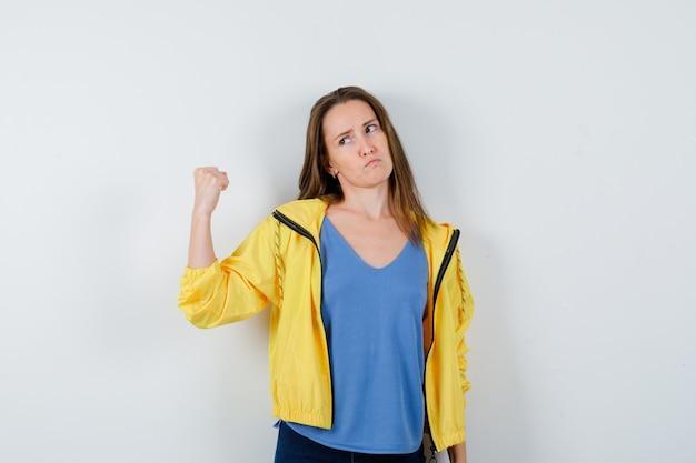 Jonge vrouw toont gebalde vuist in t-shirt, jas en ziet er zelfverzekerd uit. vooraanzicht.