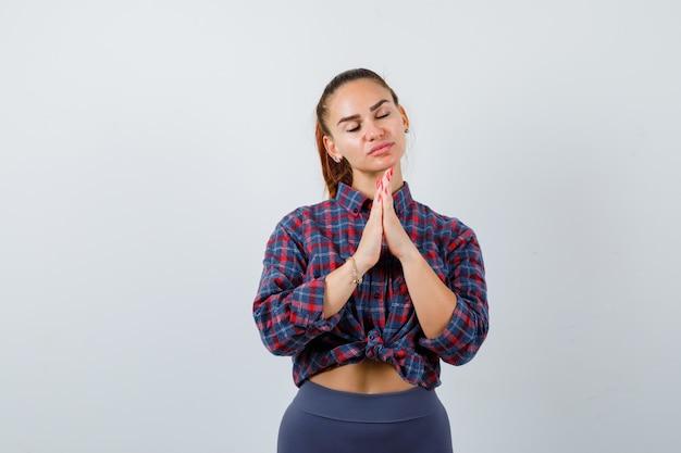 Jonge vrouw toont gevouwen handen in smekend gebaar in geruit hemd, broek en ziet er hoopvol uit. vooraanzicht.