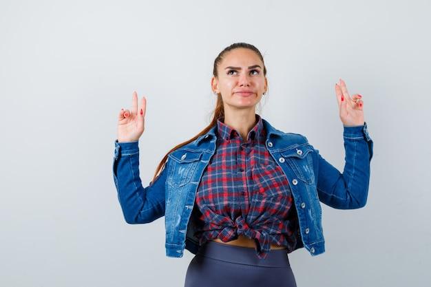 Jonge vrouw toont geweergebaar in geruit hemd, jas, broek en ziet er serieus uit. vooraanzicht.