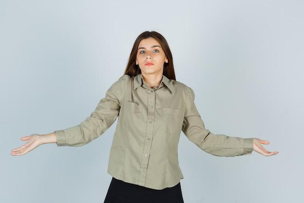 Jonge vrouw toont hulpeloos gebaar door haar schouders op te halen in shirt, rok en verward te kijken. vooraanzicht.