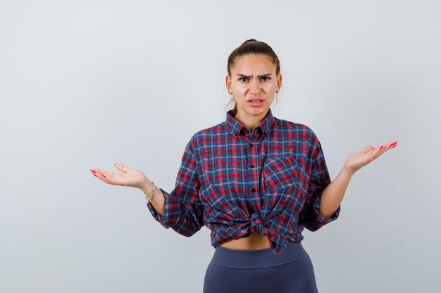 Jonge vrouw toont hulpeloos gebaar in geruit hemd, broek en ziet er gestrest uit, vooraanzicht.