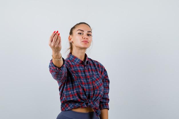 Jonge vrouw toont italiaans gebaar in geruit hemd, broek en ziet er verrukt uit. vooraanzicht.