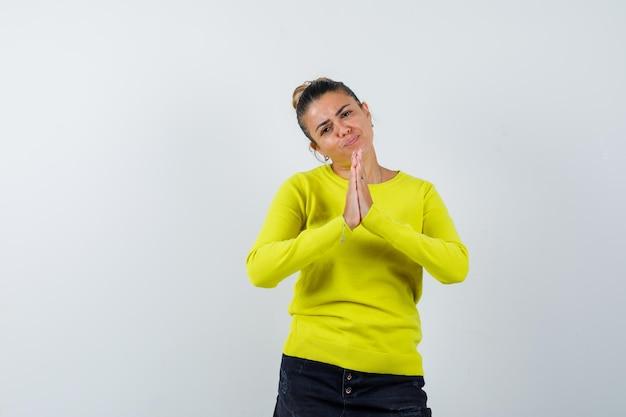 Jonge vrouw toont namaste gebaar in trui, spijkerrok en ziet er vredig uit