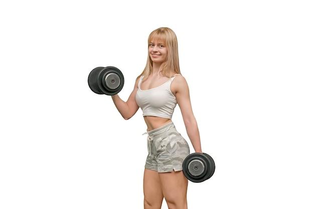 Jonge vrouw trainen met halter en zitplaatsen op een bal geïsoleerd op wit, grote zwarte rubberen halters in de handen van een klein kwetsbaar miniatuurmeisje. bodybuilder glimlachen.