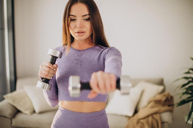 Jonge vrouw trainen met halters thuis op mat