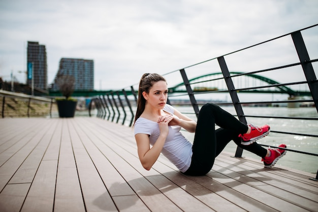 Jonge vrouw training kernspieren met sit-ups buitenshuis.
