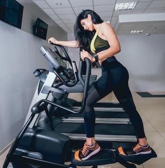 Jonge vrouw training op crosstrainer in de sportschool.