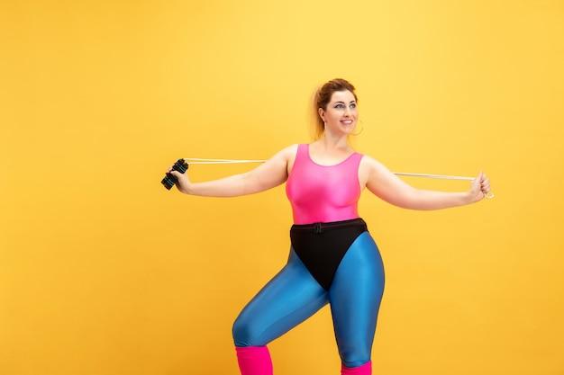 Jonge vrouw training op gele muur