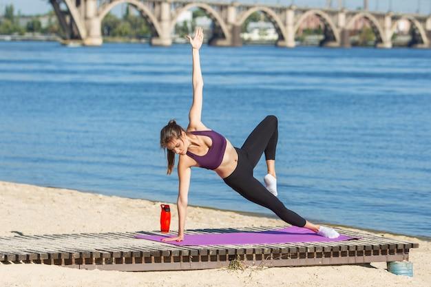 Jonge vrouw traint buiten in de herfstzon. concept van sport, gezonde levensstijl,