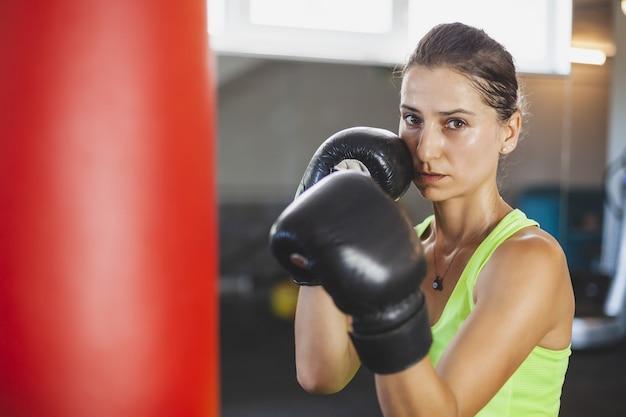 Jonge vrouw traint in de sportschool en doet boksoefeningen in bokshandschoenen voor een bokszak