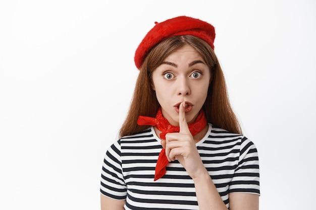 Jonge vrouw trekt wenkbrauwen op en zwijgt naar voren, drukt haar vinger op de lippen en zegt dat ze stil moet zijn, scheldend luid persoon, een geheim vertellend, staande over een witte muur