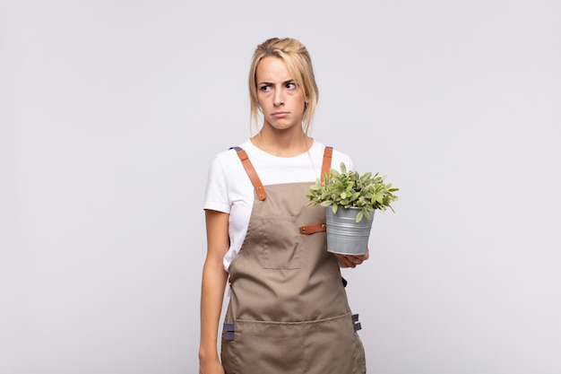 Jonge vrouw tuinman die zich verdrietig, boos of boos voelt en naar de kant kijkt met een negatieve houding, fronst in onenigheid