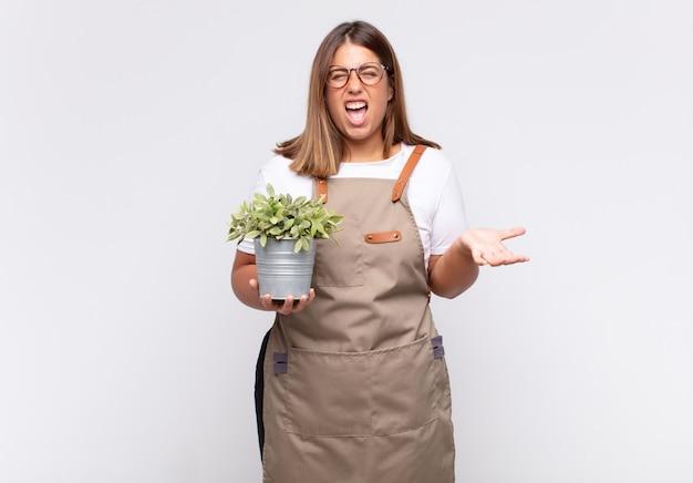 Jonge vrouw tuinman kijkt boos, geïrriteerd en gefrustreerd schreeuwend wtf of wat is er mis met je