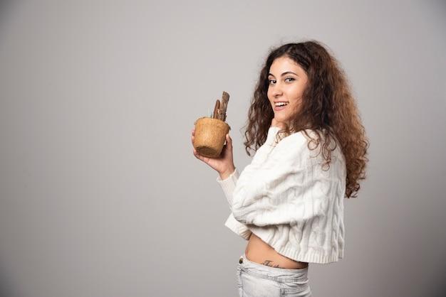 Jonge vrouw tuinman met een plant op een grijze muur. hoge kwaliteit foto