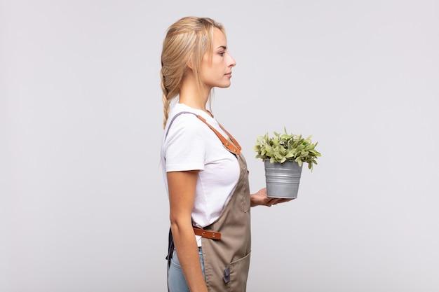 Jonge vrouw tuinman op profiel te bekijken op zoek naar ruimte vooruit te kopiëren