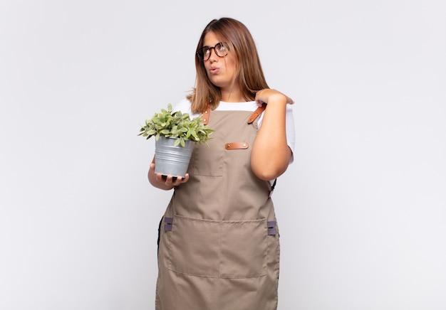 Jonge vrouw tuinman voelt zich gestrest, angstig, moe en gefrustreerd, trekt de hals van het shirt aan, kijkt gefrustreerd door het probleem