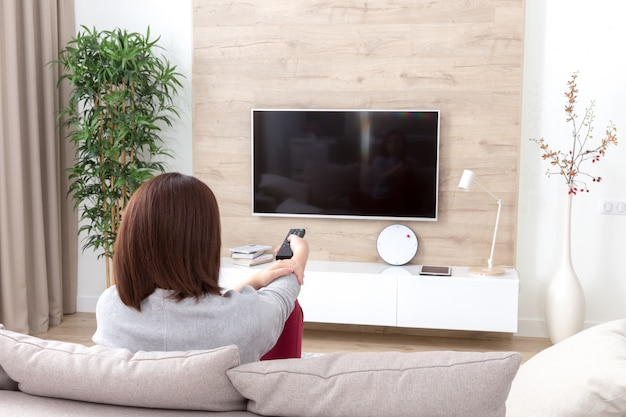 Jonge vrouw tv kijken in de kamer