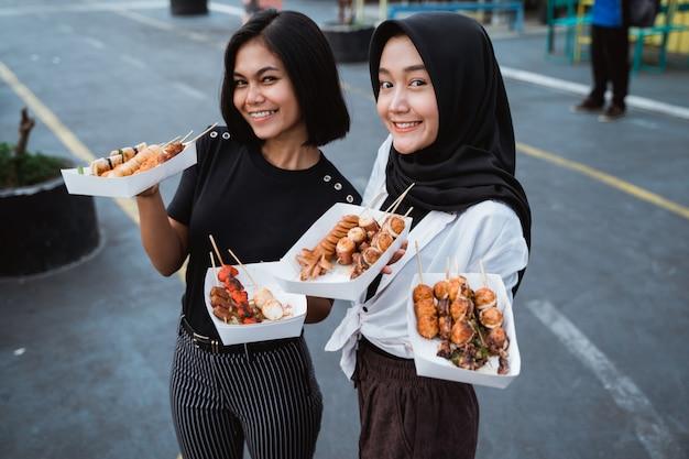 Jonge vrouw twee die een geroosterd straatvoedsel dragen