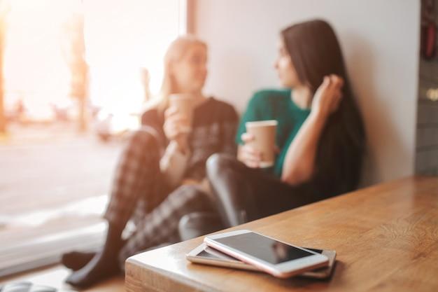 Jonge vrouw twee die in een koffiewinkel babbelt. twee vrienden genieten van koffie samen. hun smartphones liggen in stapel op tafel op de voorgrond