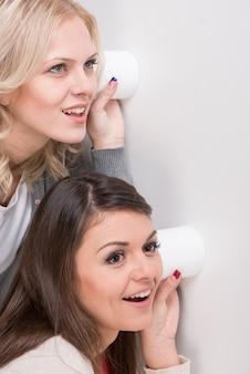 Jonge vrouw twee gebruikt een glas als telefoon.
