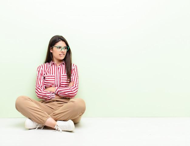 Jonge vrouw twijfelt of denkt, bijt op lip en voelt zich onzeker en nerveus, op zoek naar ruimte aan de zijkant zittend op de vloer