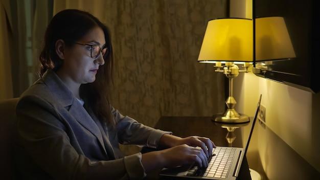Jonge vrouw typt op een laptop onder het licht van een tafellamp