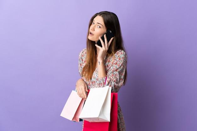 Jonge vrouw uit ierland geïsoleerd op paarse muur met boodschappentassen en een vriend bellen met haar mobiele telefoon