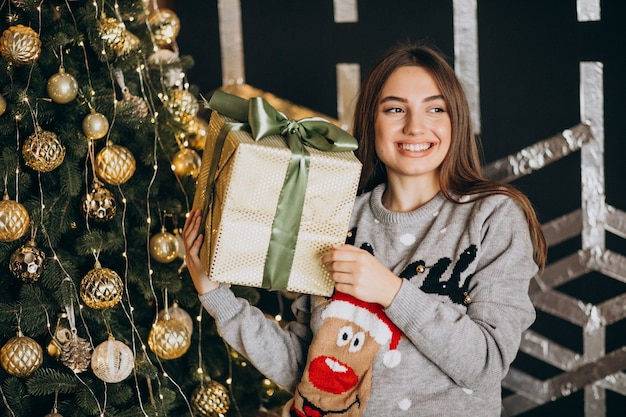 Jonge vrouw uitpakken kerstcadeau door de kerstboom