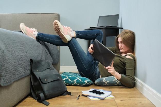 Jonge vrouw universiteitsstudent die digitale tablet-pc leest, online onderwijs, afstandsonderwijs. slim meisje met bril zittend op de vloer