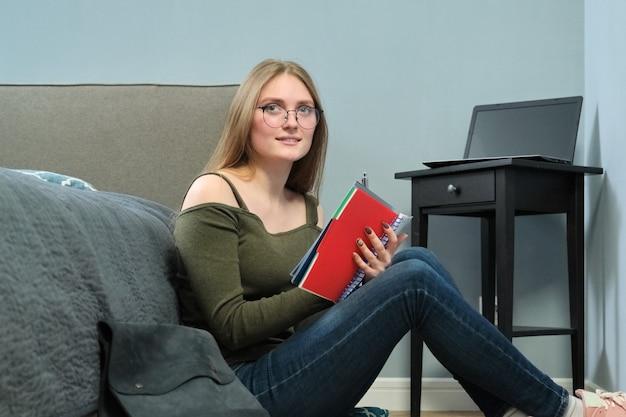 Jonge vrouw universiteitsstudent met leerboeken lezen en studeren thuis, leren op afstand. slim meisje met bril zittend op de vloer