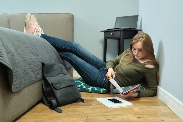 Jonge vrouw universiteitsstudent om thuis te zitten op de vloer en studeren met behulp van boeken