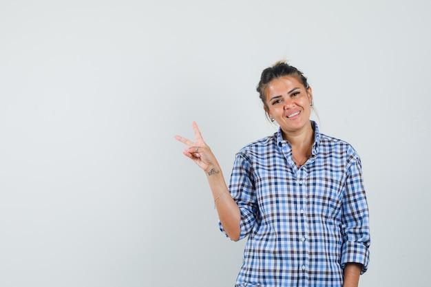 Jonge vrouw v-teken in geruit overhemd tonen en vrolijk kijken.