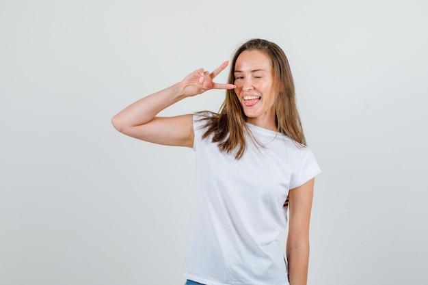 Jonge vrouw v-teken met knipperende ogen in t-shirt, korte broek en energiek kijken. vooraanzicht.