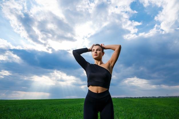 Jonge vrouw van atletische bouw met een zwarte top en zwarte legging op een achtergrond van blauwe lucht. gezonde levensstijl, atletisch donkerbruin meisje. het concept en de motivatie van sport