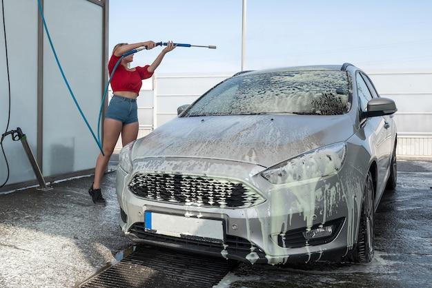 Jonge vrouw van de bestuurder uit een hogedrukslang past zeepschuim toe op de auto voor het reinigen van vuil bij handmatige wasstraat
