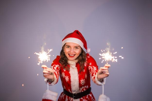 Jonge vrouw van de kerstman in rode kerst of nieuwjaar jas en hoed met sterretje en bengalen vuur.