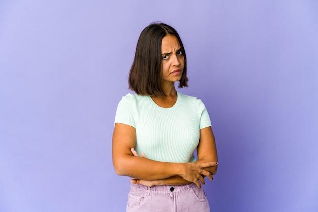 Jonge vrouw van gemengd ras die achterdochtig, onzeker is en u onderzoekt.