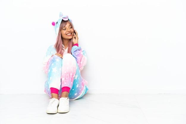 Jonge vrouw van gemengd ras die een eenhoornpyjama draagt die op de vloer zit geïsoleerd op een witte achtergrond en een gesprek voert met de mobiele telefoon met iemand