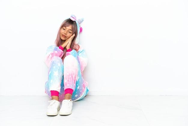 Jonge vrouw van gemengd ras die een eenhoornpyjama draagt die op de vloer zit geïsoleerd op een witte achtergrond en slaapgebaar maakt in schattige uitdrukking