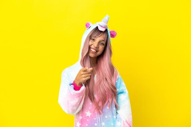 Jonge vrouw van gemengd ras die een eenhoornpyjama draagt, geïsoleerd op een witte achtergrond, wijst de vinger naar je met een zelfverzekerde uitdrukking