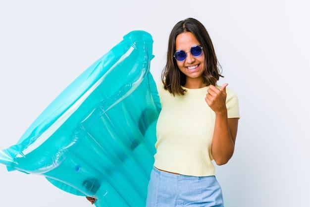 Jonge vrouw van gemengd ras die een luchtbed vasthoudt en beide duimen opsteekt, glimlachend en zelfverzekerd.