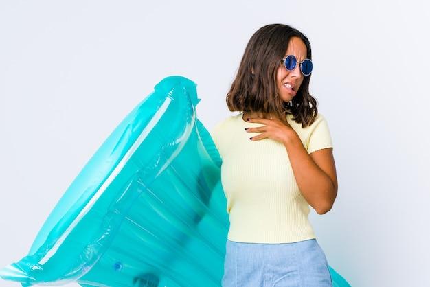 Jonge vrouw van gemengd ras die een luchtbed vasthoudt en de achterkant van het hoofd aanraakt, denkt en een keuze maakt.