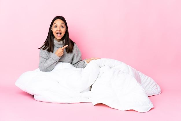 Jonge vrouw van gemengd ras die een pijama draagt die verrast op de grond zit en naar de zijkant wijst