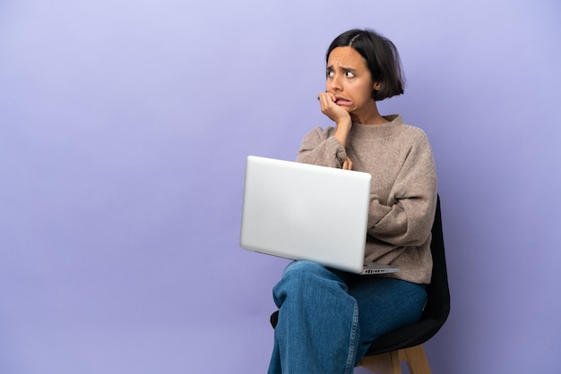 Jonge vrouw van gemengd ras die in een stoel zit met een geïsoleerde laptop is een beetje nerveus